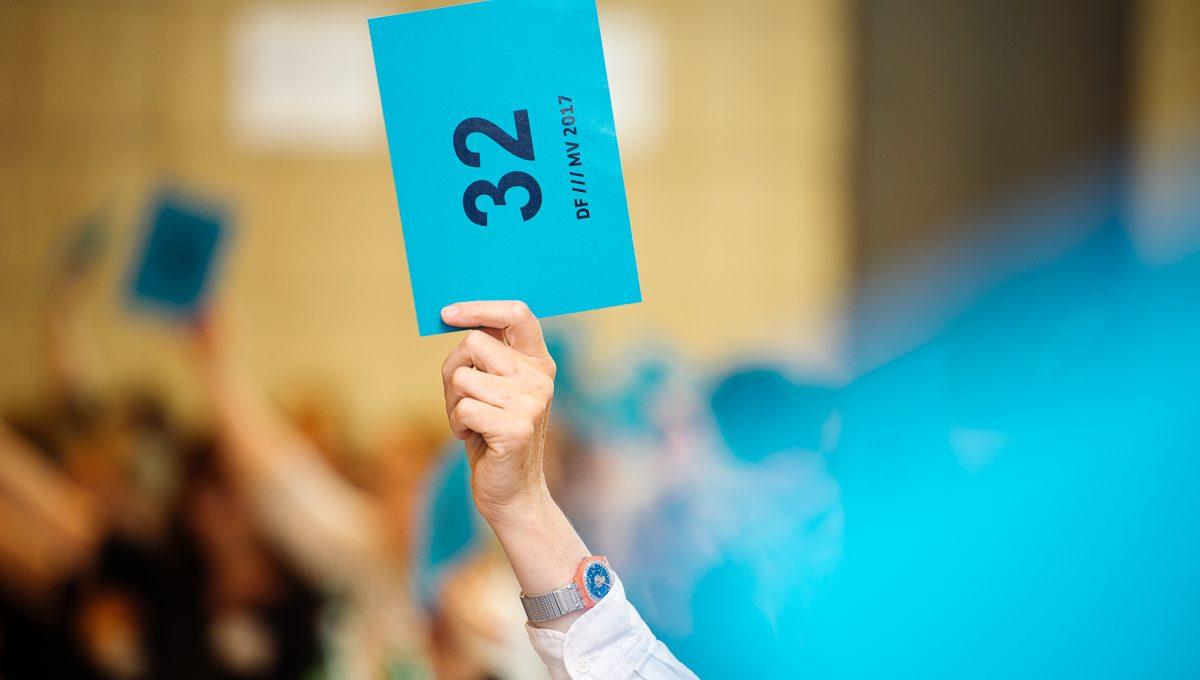 Erhobene Hand mit Stimmkarte, im Hintergrund weitere erhobene Hände