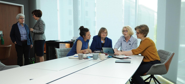 Vier Frauen sitzen um einen Tisch und sehen auf einen Laptop. Zwei Frauen stehen neben dem Tisch und unterhalten sich.