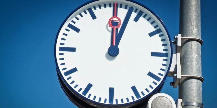 Uhr an einem Bahngleis vor blauem Himmel. Die Uhr zeigt drei Minuten nach Zwölf Uhr an.